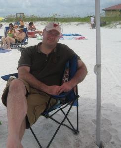 My husband sitting under our beach umbrella